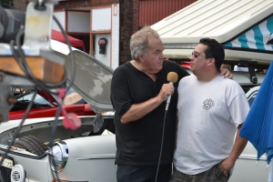 Comcast's Motorsports host Bill Wildt interviews car owner.